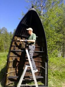 Boman tjärar ekan vid infarten till Föreningen Allmogebåtar